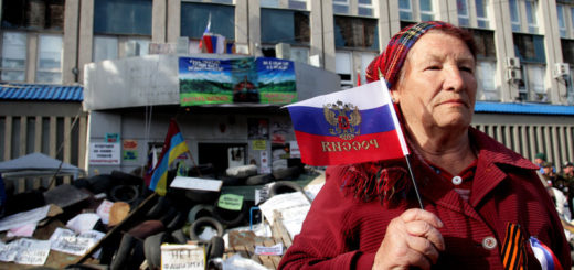 epa04169142 An elderly woman with Russian flag poses in front of the occupied security service building in Lugansk, Ukraine, 16 April 2014. According to media reports, about six armored personnel carriers, which were seized by armed pro-Russian protesters in Kramatorsk, arrived to the eastern Ukrainian town of Slaviansk.  EPA/ZURAB KURTSIKIDZE
