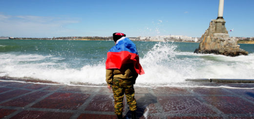 epa04129737 A man drapes the Russian flag on his shoulders as he stands on the coast of the bay of Sevastopol, Crimea, Ukraine, 17 March 2014. More than 95 per cent of Crimeans who had taken part in referendum voted for reunification of Crimea with Russia. On 18 March Russian President Vladimir Putin is to address the Russian Federal Assembly on the Crimea's and the city of Sevastopol's requests to be admitted into Russia.  EPA/ZURAB KURTSIKIDZE