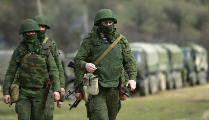 Armed men, believed to be Russian servicemen, march outside an Ukrainian military base in Perevalnoye, near the Crimean city of Simferopol March 13, 2014. President Vladimir Putin said on Thursday Russia was not to blame for the crisis over Ukraine's Crimea region. REUTERS/David Mdzinarishvili (UKRAINE - Tags: POLITICS CIVIL UNREST MILITARY)